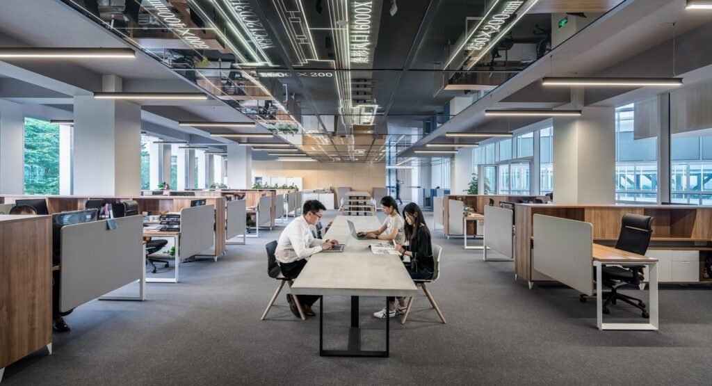 Office environment with three people working on laptops